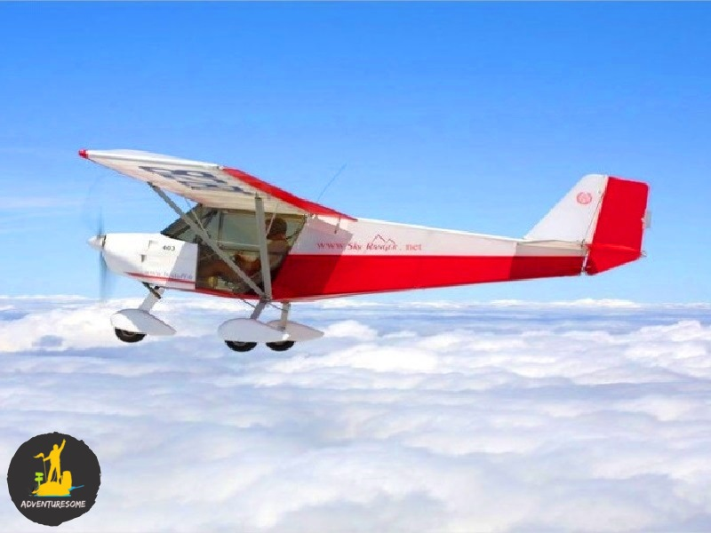 Microlight flying above clouds